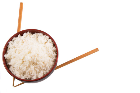 A bowl of rice and a pair of chopstick over white background photo