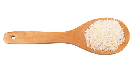 Raw and uncooked rice in wooden spoon over white background photo