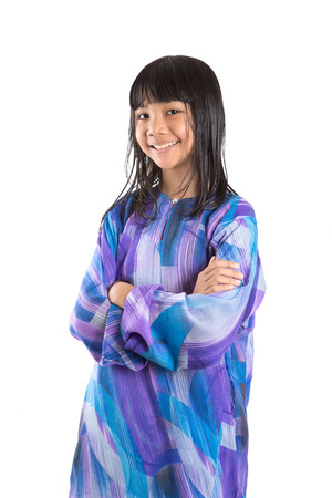 Young preteen Asian girl in Malay traditional dress baju kurung over white background Stock Photo