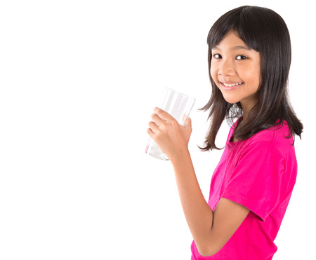 Young Asian preteen with a glass of water over white background Stock Photo