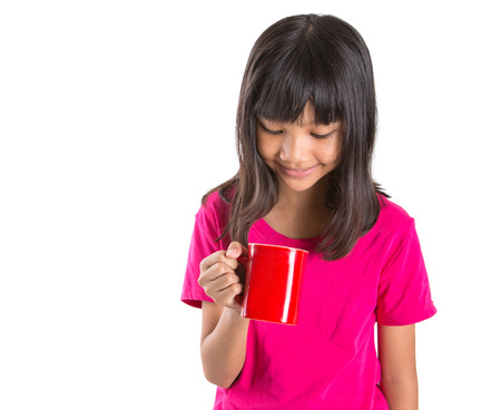 preteen girl: Young Asian preteen girl with a red mug over white background