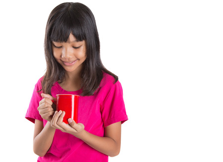 asian preteen: Young Asian preteen girl with a red mug over white background