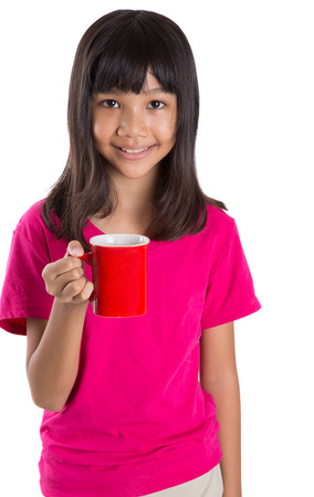 preteen model: Young Asian preteen girl with a red mug over white background