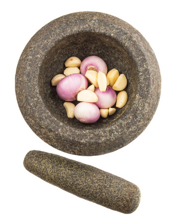 Stone mortar and pestle with onions and garlic over white background photo