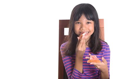 preteen girl: Young Malay Asian preteen girl having breakfast