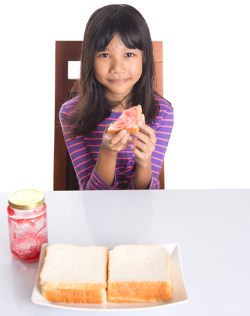 Young Malay Asian preteen girl having breakfast