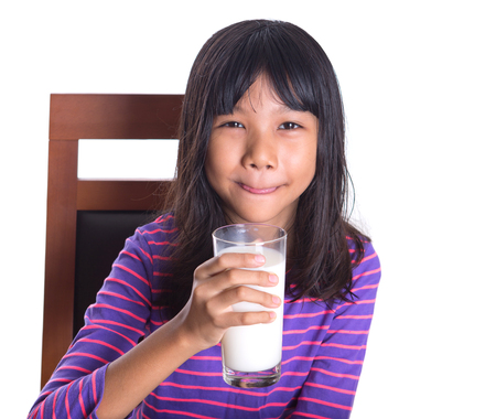 Young Asian preteen girl with a glass of milk