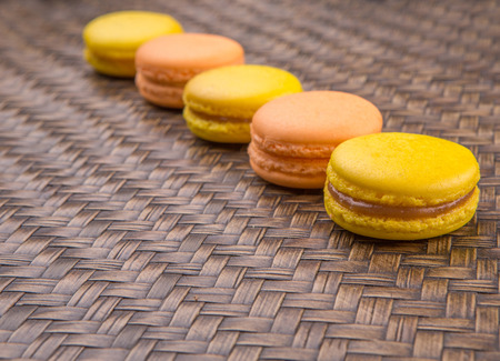 Yellow and orange colored French macarons on wicker background photo