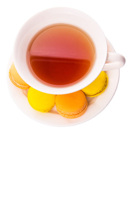 A cup of tea and yellow and orange colored macarons over white background photo