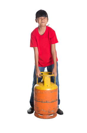 asian preteen: Young Asian girl moving an old cooking gas propane cylinder over white background Stock Photo