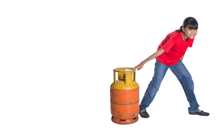 Young Asian girl moving an old cooking gas propane cylinder over white background Stock Photo