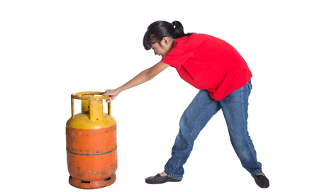 old asian: Young Asian girl moving an old cooking gas propane cylinder over white background Stock Photo