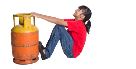 working model: Young Asian girl moving an old cooking gas propane cylinder over white background Stock Photo
