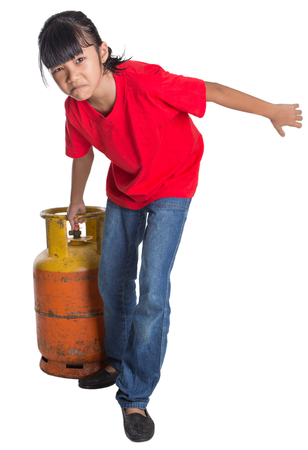 asian cooking: Young Asian girl moving an old cooking gas propane cylinder over white background Stock Photo