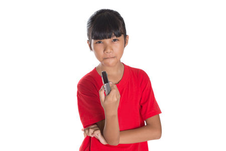 changing channels: Young Asian girl with television remote control device over white background