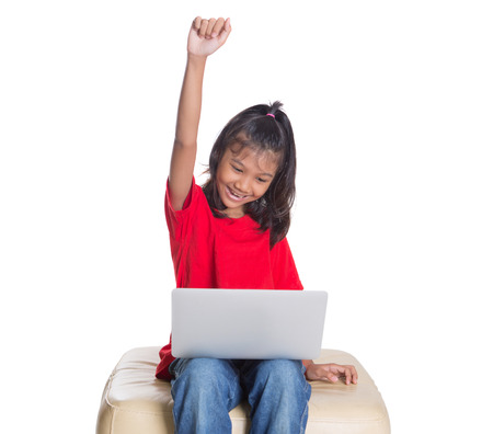Young Asian girl with a laptop raising her arms over white background photo