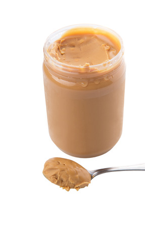 An opened jar of peanut butter with a small spoon photo