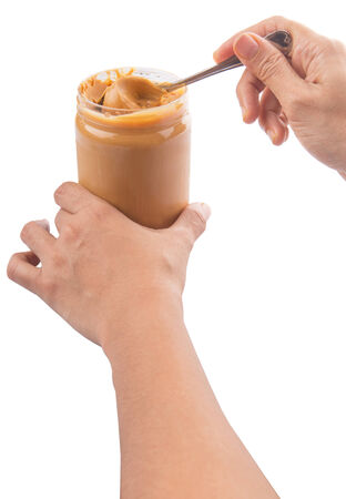 Female hand with peanut butter over white background photo