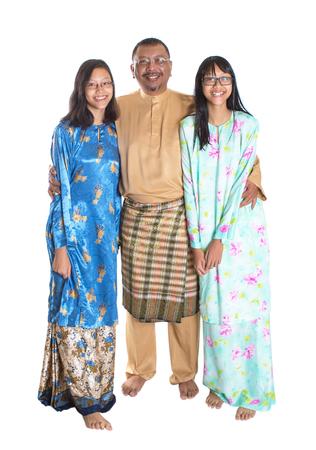 age related: Middle age Asian Malay father and teen daughters in traditional attire over white background