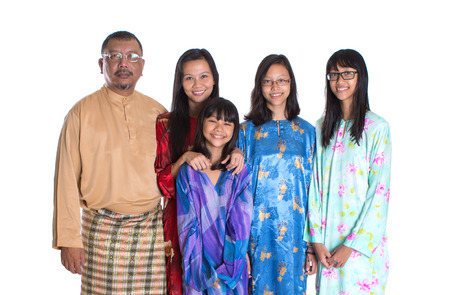 age related: Asian Malay parents with teen daughters in traditional attire over white background