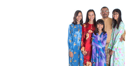 Asian Malay parents with teen daughters in traditional attire over white background