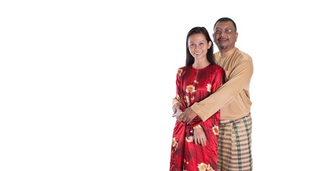 mid adult: Middle age Malay couple in traditional dress over white background