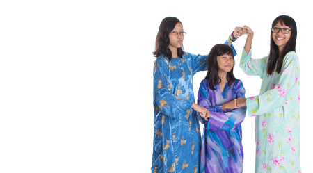 Malay teenage sisters in traditional attire over white background Stock Photo