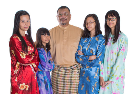 Asian Malay parents with teen daughters in traditional attire over white background photo