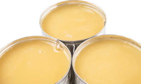 sweetened: Condensed milk in tin can over white background Stock Photo