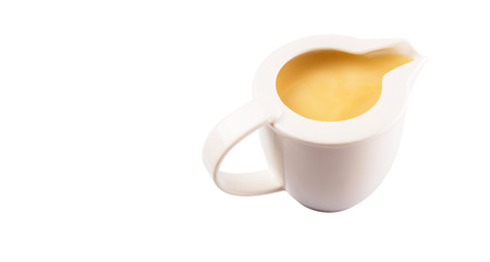 sweetened: Condensed milk in a small milk jug over white background Stock Photo