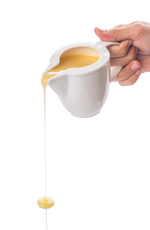 creamer: Female hand pouring condensed milk over white background