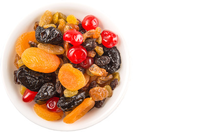 Mix variety of dried fruit in white bowl over white background photo