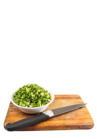 Chopped scallions or spring onion leaves in a white bowl with a cutting knife on a wooden cutting board Stock Photo