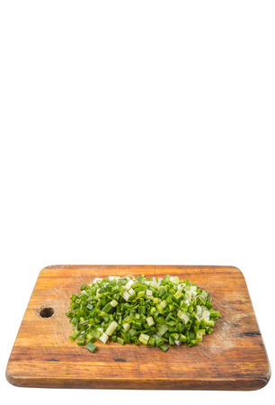 Spring onion or scallions on wooden cutting board over white background