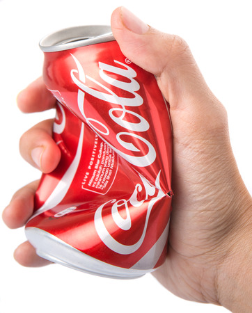 crushed cans: KUALA LUMPUR, MALAYSIA - JANUARY 14TH, 2015. Crushing empty can of Coca Cola