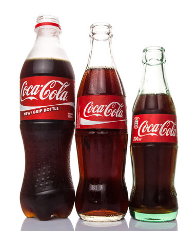addictive drinking: KUALA LUMPUR, MALAYSIA - JANUARY 6TH, 2015. Bottles of Coca Cola soft drinks. Coca Cola drinks are produced and manufactured by The Coca-Cola Company, an American multinational beverage corporation.