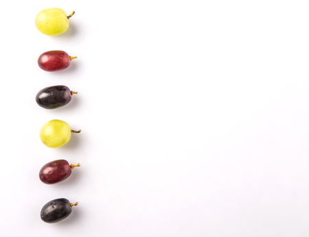 Red, green and black grapes fruits over white background