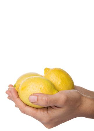 yellowrn: Female hand holding lemon fruit over white background Stock Photo