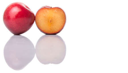 drupe: A slice of victoria plum or red plum over white background