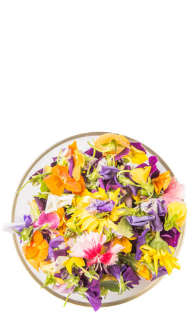 Mix edible flower salad in a glass bowl over white background