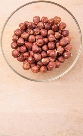 cobnut: Hazelnuts in a glass bowl on wooden cutting board