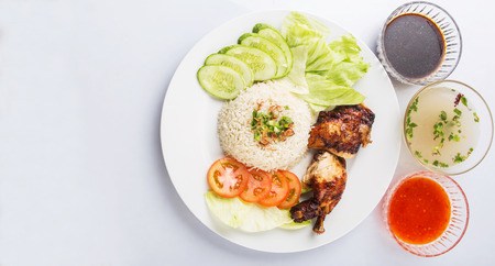 popular soup: Popular Malaysian dish Nasi Ayam or chicken rice with baked chicken pieces, tomato, cucumber, salad, soup, soy sauce and chili sauce.