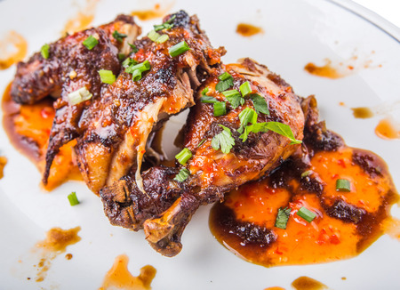 chili sauce: Roasted chicken piece coated with soy sauce and chili sauce on white plate