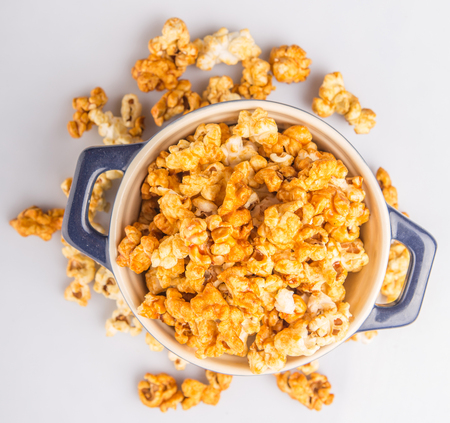 popcorn kernel: Caramel popcorn in blue pot over white background