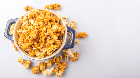 starchy food: Caramel popcorn in blue pot over white background