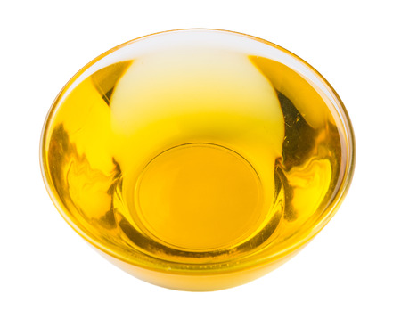 Vegetable cooking oil in a clear glass bowl over white background