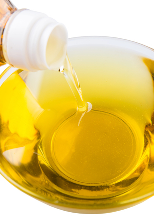 cooking oil: Pouring vegetable cooking oil into a clear glass bowl