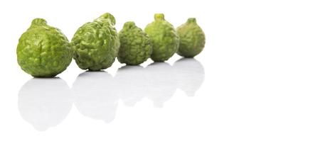 Kaffir or makrut lime over white background photo