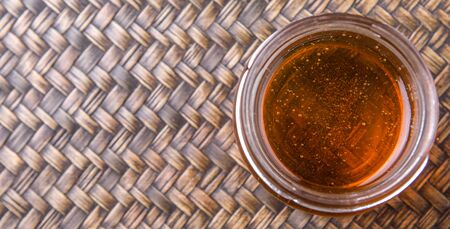 curative: Honey in a mason jar on a wicker background Stock Photo