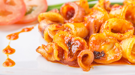 squid: Malaysian dish of fried squid with hot and spicy sambal or chili gravy with scallion and tomatoes on white plate.